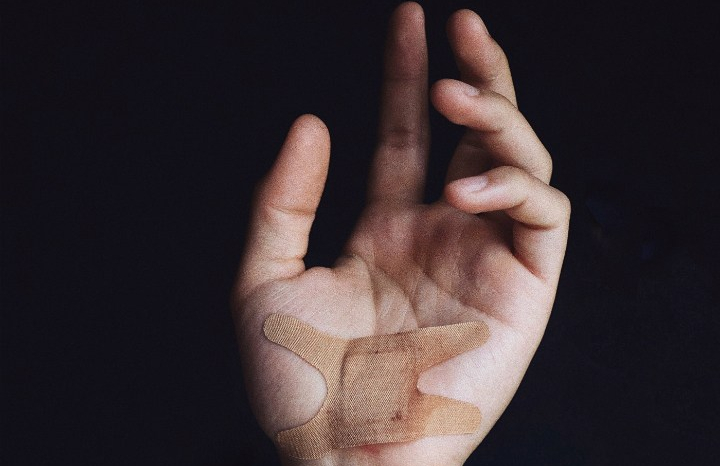 A hand is shown against a black background with a bandage covering the palm.