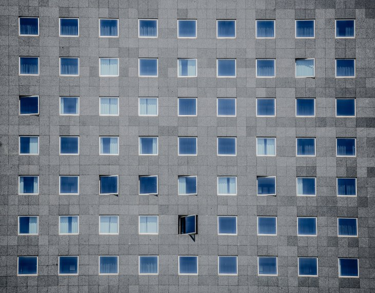 A number of blue-tinted windows from a gray building are facing forward.