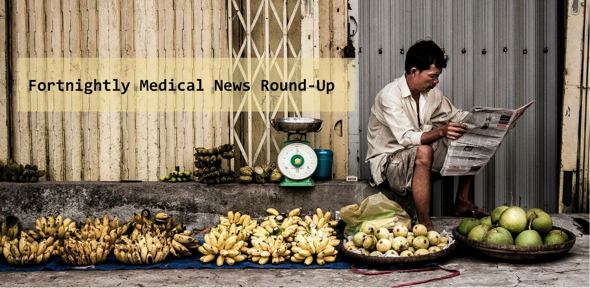 "A man is reading a newspaper behind a street fruit stand and next to a scale for fruit with the title ""Fortnightly Medical News Round-Up"" next to him."