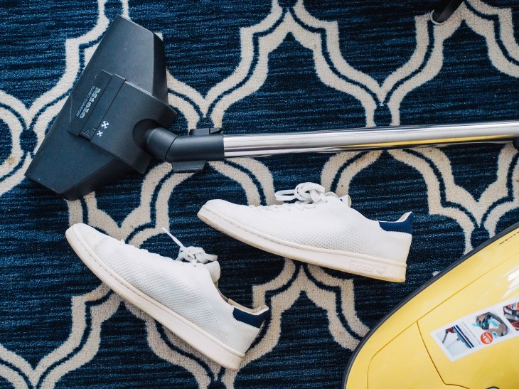 A vacuum rests near a pair of white shoes against a blue and white carpet.