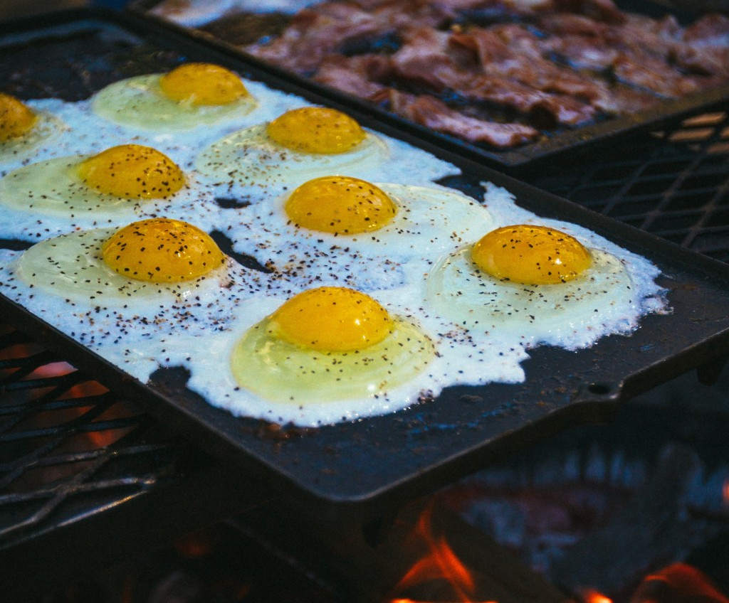 Several eggs are on a tray frying over a fire next to some frying bacon.