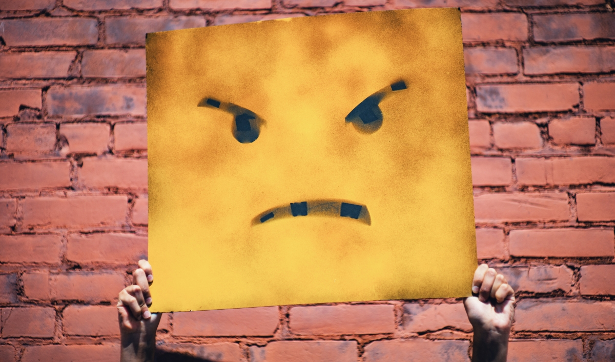 Against a brick wall background, two hands are holding up a sign with an angry face on it.
