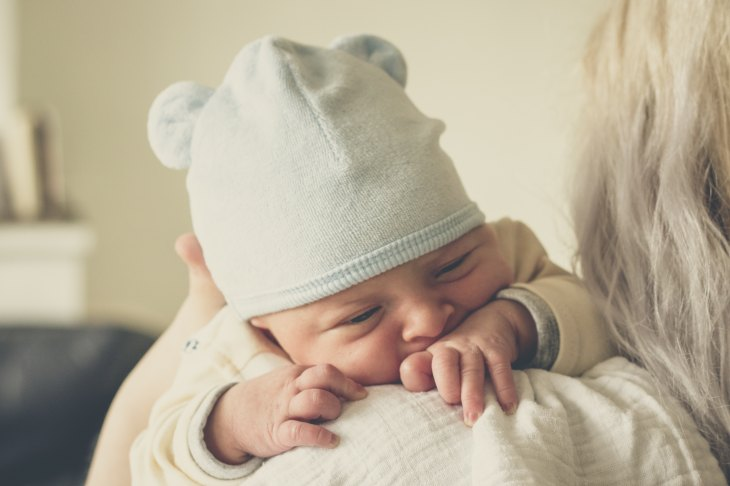 A baby in a bear-head-shaped hat is holding on to their mother's shoulder.