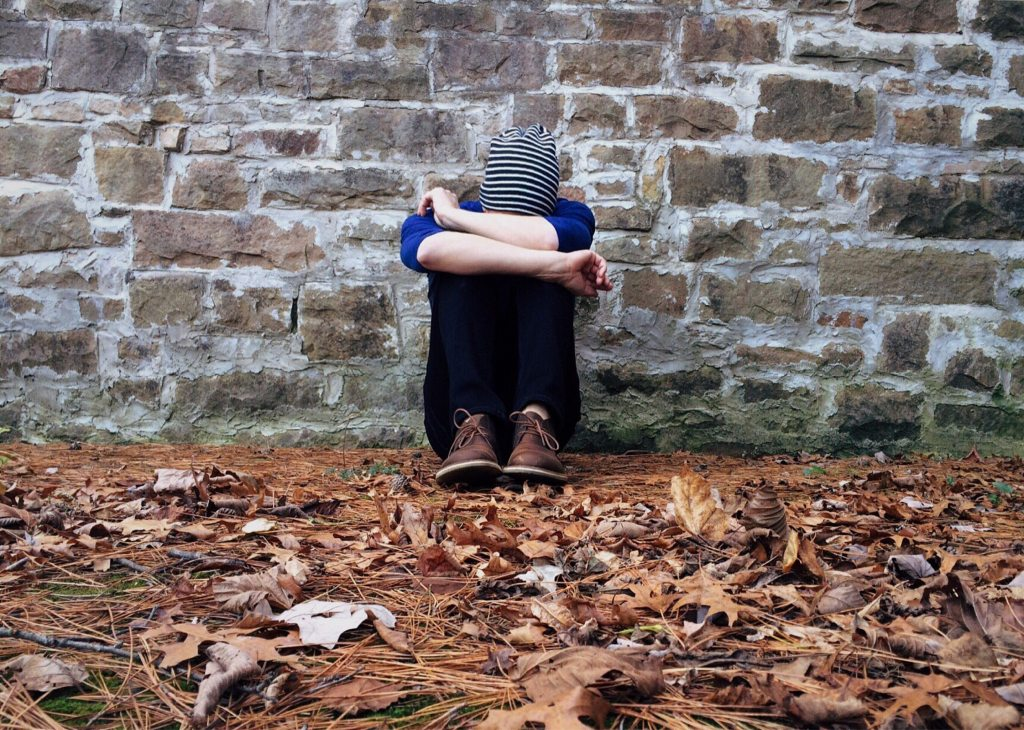 An adult is hugging their knees on leaf-covered ground next to a brick building.