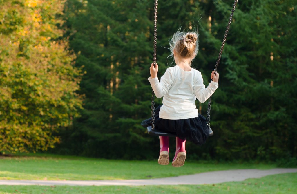 A young girl is on a swing in a wooded area.