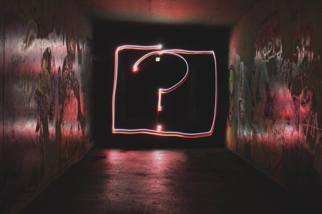 A bright neon question mark is surrounded by an equally bright neon square in a grimy hallway.